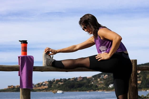 Continúa rehidratándote durante el calentamiento físico - mujer estirando junto a botella con agua