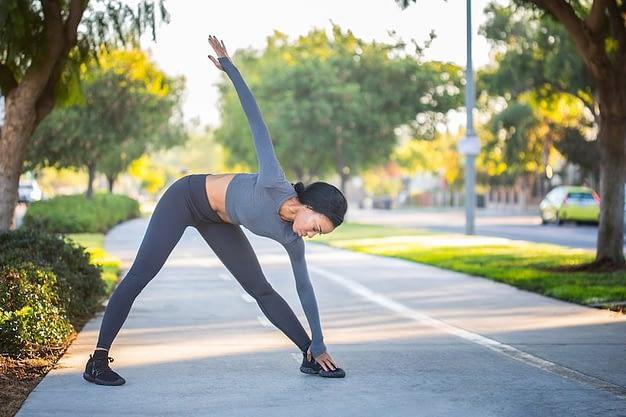 Calentamiento físico general, estiramiento físicos - mujer estirando en la calle