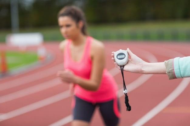 Valoración de la condición físicas del opositor para preparar las pruebas físicas a las oposiciones - mujer corriendo en una pista de atletismo mientras es cronometrada su carrera