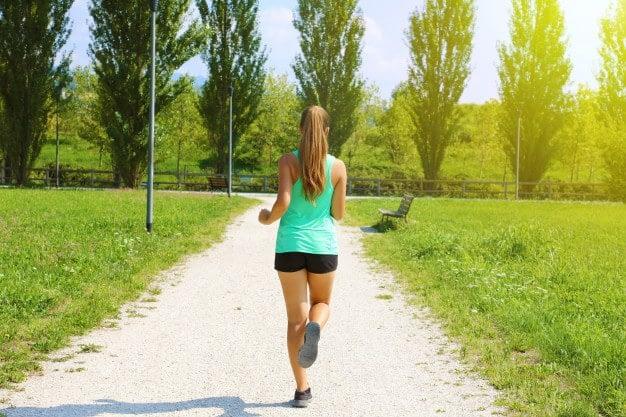 Calentamiento físico general, carrera suave - mujer corriendo por un camino